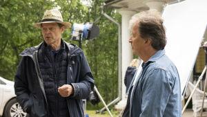 två äldre män som står på en filminspelningsplats.