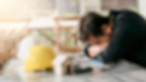 Suddig bild av en person som sitter vid ett bord lutar huvudet på armarna mot bordet.