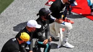 Lewis Hamilton knäböjer tillsammans med tre andra förare.