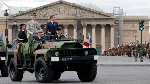 President Macron ståendes till höger uppe på fordonet.