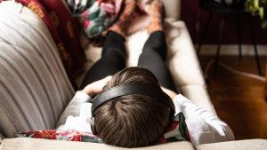 Nainen kuuntelee korvakuulokkeet päässä sohvalla maaten.