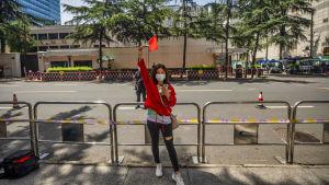 Kvinna med mörkt hår står utanför konsulat och håller upp Kinas flagga. Kvinnan är klädd i röd jacka och bär munskydd.