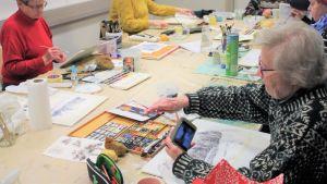 Äldre människor som sitter runt ett bord och målar med akvarell färg.