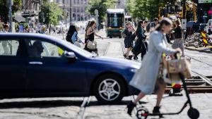 En gatuvy med en blå bil, flera fotgängare en spårvagn och gatuarbeten i Helsingfors centrum i juli 2020.