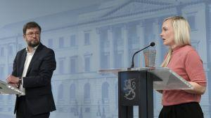 Marial Ohisalo i ljusröd topp och Timo Harakka i kavaj. Båda står vid podium under regeringens presskonferens.
