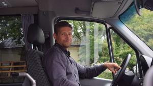 En man bakom  ratten på en buss. han ler lite när han ser in i kameran.