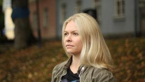 En blond kvinna står vid åstranden i Åbo och tittar bort från kameran.