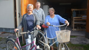 tre glada människor med cyklar framför ett garage.