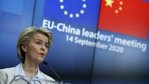 Ursula von der Leyen. I bakgrunden EU:s och Kinas flaggor.