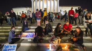 Folk har samlats med ljus, blommor och plakat utanför USA:s högsta domstol för att sörja Ruth Bader Ginsburg.