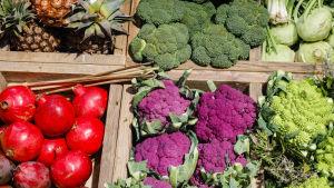Grönsaker och frukter, bland annat broccoli och granatäppel, i ett stånd.