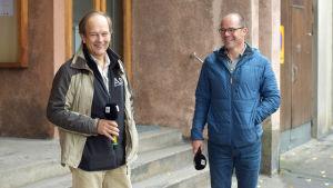 Två skrattande män på en trottoar.