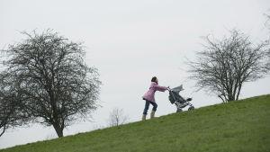 En kvinna går upp för en kulle med en barnvagn.
