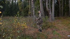 Man med pilbåge rör sig i skogen.