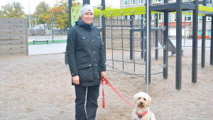 Kvinna med hund på en skolgård