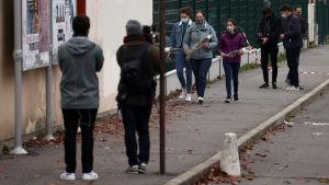 Unga men munskydd hämtar med sig blommor till en skola i Conflans-Sainte-Honorine där en lärare har mördats.