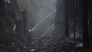 Brandmän sprutar vatten i en gråsvart omgivning av brunna husrester.