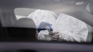 Coronatesttagning görs som drive-in, sjukvårdare i skyddsutrustning tar testet på person som sitter i bil.