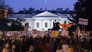 En folksamling med skyltar framför vita huset.