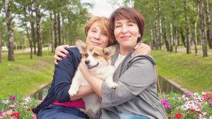 Två kvinnor sitter bredvid varandra utomhus. De har armarna om varandra och om en hund som de har i famnen.