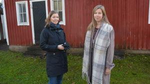 Två kvinnor står framför ett rött hus.