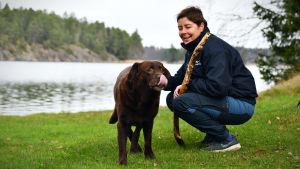 Birgitta Lindholm och hunden Bamse på stugan i Barösund.