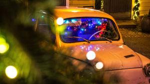 Festlig julbelysning och en gammaldags bil på gatan
