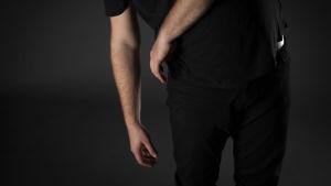Bild på Jonas torso, där händerna hänger och dinglar mot marken. Huvudet syns inte, i en mörklagd studio.