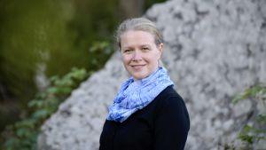 En kvinna iklädd en blå halsduk, står utomhus framför en stor sten.