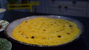 Ett ogräddat vetebröd som är gult av saffran och garnerat med mandel och russin. Saffranskakan jäser i en pajform.