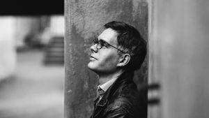 En svartvit bild av en man med glasögon i profil.