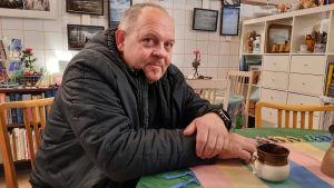 En man i svart jacka sitter vid ett bord med en kaffekopp framför sig. Han ler lite och tittar in i kameran.