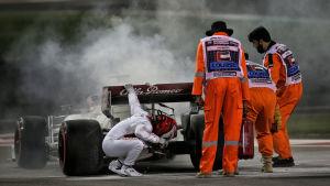 Kimi Räikkönen inspekterar sin bil.