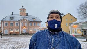 Petteri står iklädd ett munskydd och ler i Borgå gamla stad.