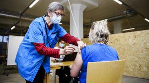 En person som jobbar inom hälsovården får coronavaccin.