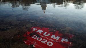 En röd skylt med texten Trump 2020 Make America Great har hamnat bland döda löv i en vattenpöl.