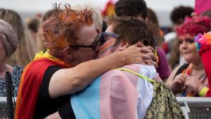 Två kvinnor kysser varandra i samband med en Pride-parad.