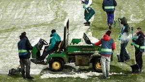 Planfunktionärer lastar bort snö från gräset.