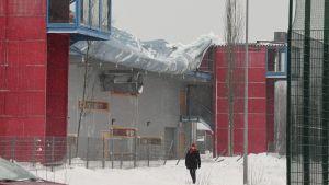 En idrottshall vars tak rasat in. I förgrunden en person med röd mössa. Hallens väggar är röda och grå.