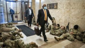 Bild på soldater som sover i USA:s kongressbyggnad och en kostymklädd man går i mitten.