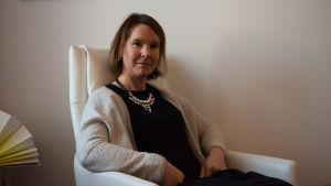 En kvinna sitter i en vit fåtölj, vägg i bakgrunden.