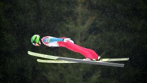 Ilkka Herola flyger vågrätt genom luften i ett backhopp.