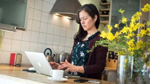 En kvinna står och jobbar vid en bärbar dator.