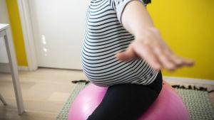 En gravid kvinna sitter på en gympaboll.