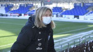 Anna Signeul står med ryggen mot fotbollsplanen.