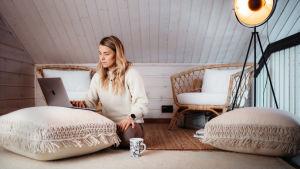Nainen istuu lattialla, läppäri isolla tyynyllä edessään.