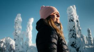 Nainen hymyilee tyytyväisen näköisenä lumisten puiden välissä.