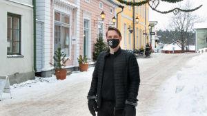 En man står i vintrigt Gamla stan i Borgå, han har svart munskydd på sig.