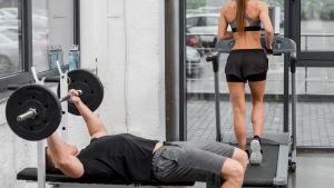 I förgrunden en man som lyfter vikter på gym, i bakgrunden en kvinna som springer på löpmatta.