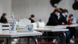 Handdesinficeringsmedel och munskydd på ett bord i ett klassrum.